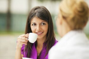 A woman speaking to another woman over a cup of coffee
